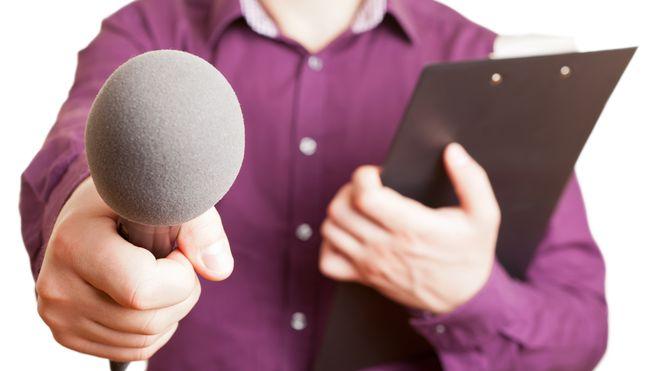 Mann von der Presse hält ein Klemmbrett und ein Mikrofon